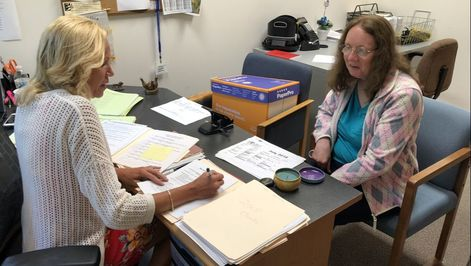 Picture of caseworker with client filling out paperwork